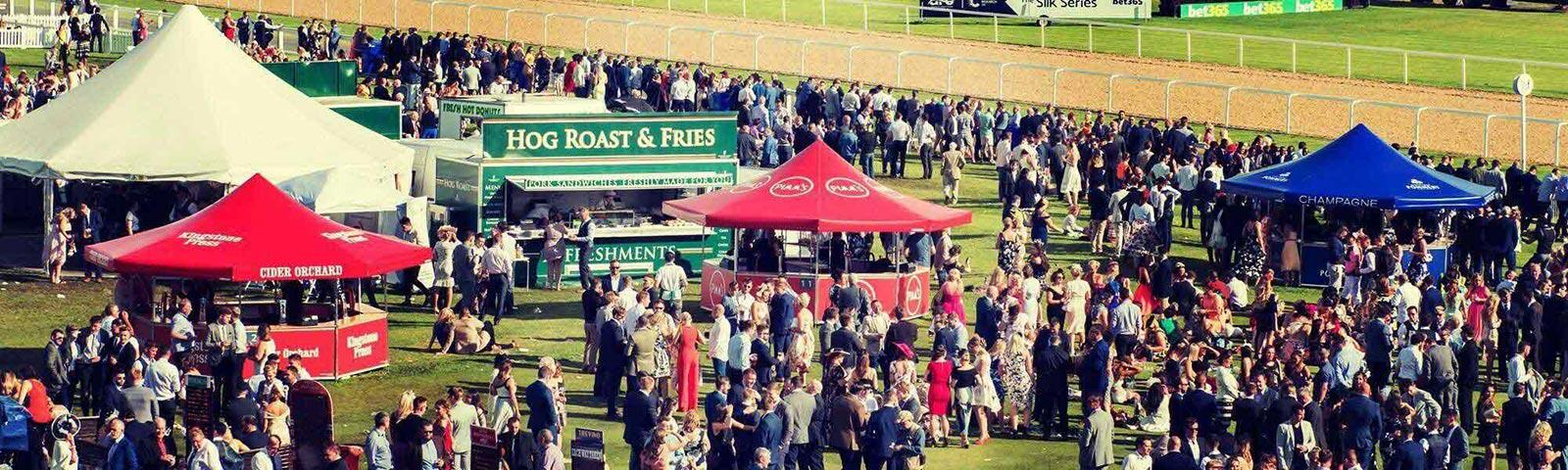 Crowds gathered around bars and food stands at Newcastle Racecourse during a raceday.
