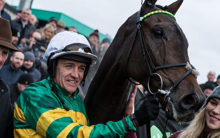 A Jockey celebrates his run with horse and training staff