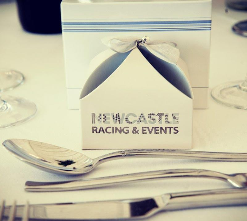 A section of a table at Newcastle Racecourse with fresh white tablecloth and sparkling silverware.