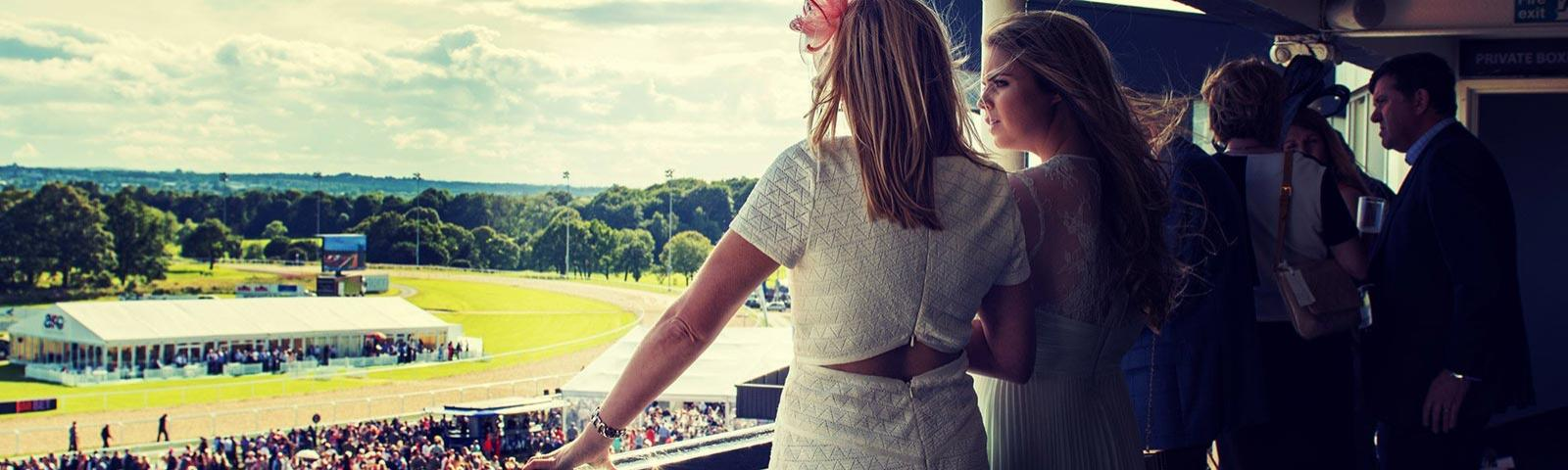 A group enjoy the view over Newcastle Racecourse from a hospitality area.
