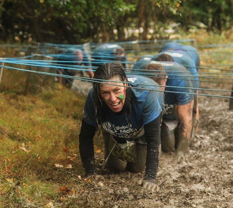 Group of people tackling an obstacle during the Stampede at Newcastle Racecourse.