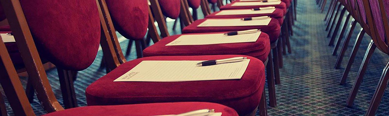 Rows of red chairs, each with a pen and notepad resting on the seat.