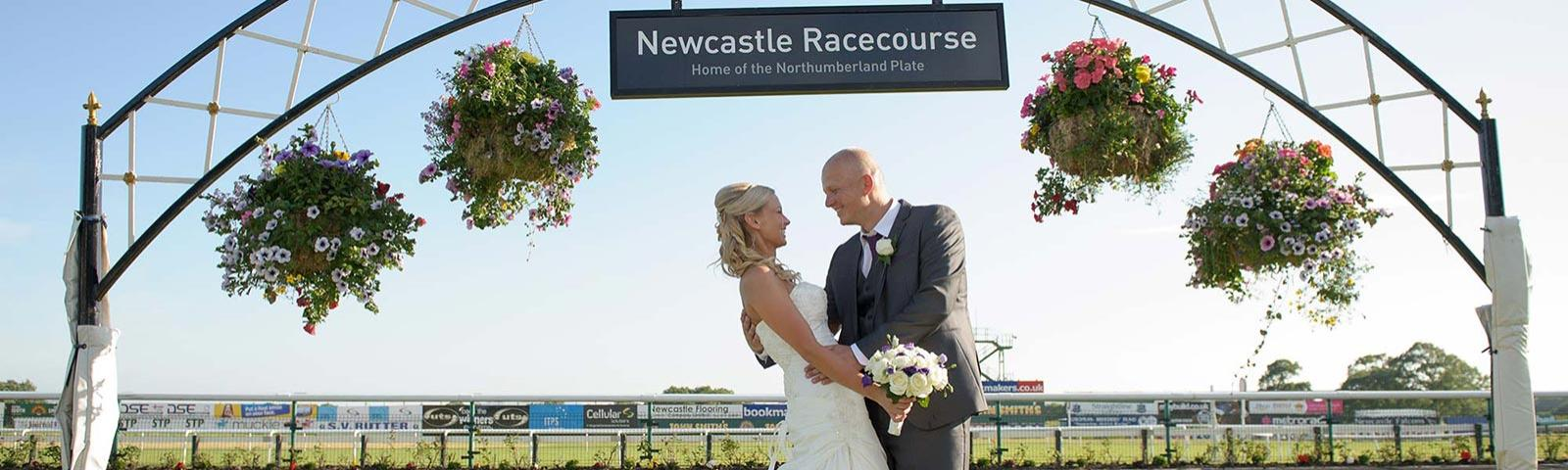 Bride and Groom embrace beneath a decorative Arch on their Wedding day at Newcastle Racecourse