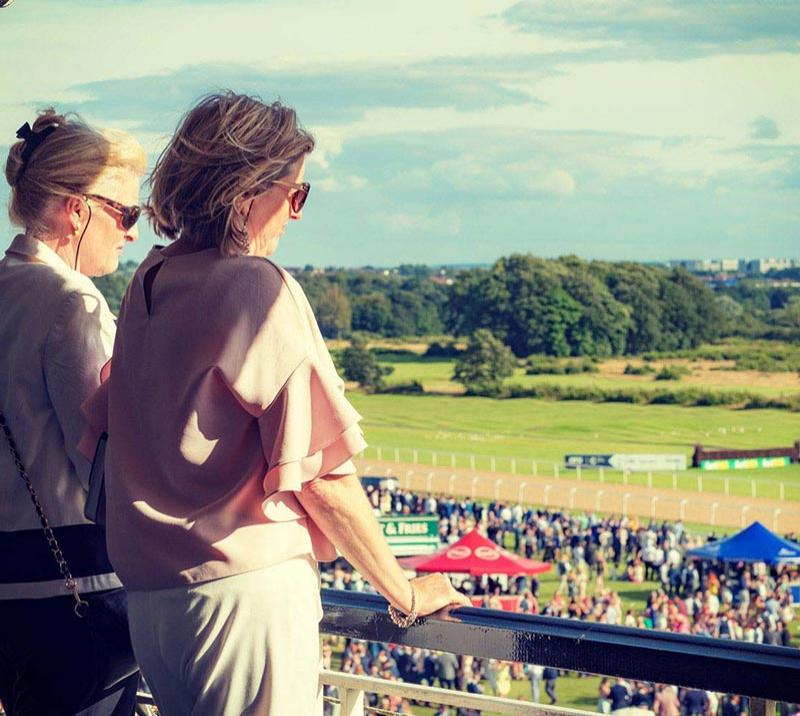 Two ladies in a hospitality area watch over the events on the course at Newcastle Racecourse