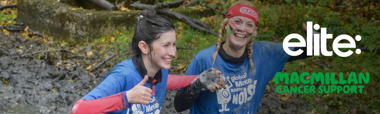 Two ladies are battling through the mud.  On the right are logos for Stampede sponsors elite: and Macmillan Cancer Support