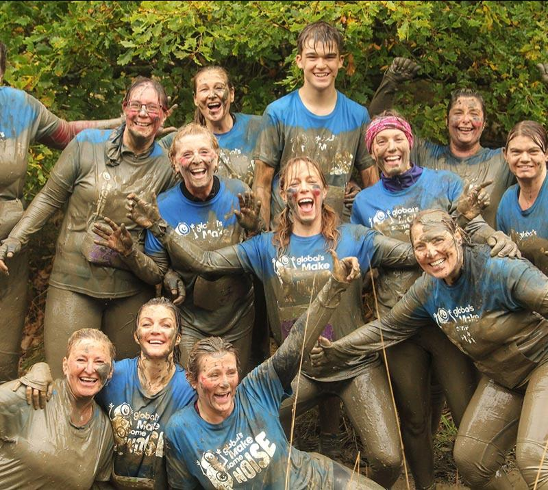 A large group covered in mud celebrate their success at Newcastle Stampede hosted at Newcastle Racecourse