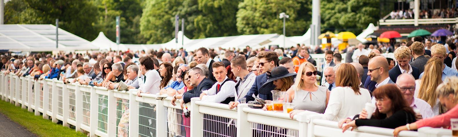Crowds watching racing at Newcastle Racecourse.