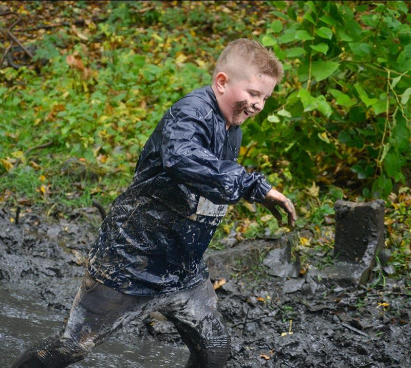 A teenage boy struggles through a muddy obstacle at Newcastle Stampede hosted at Newcastle Racecourse