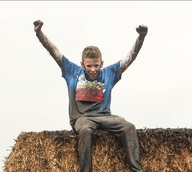 A teenage boy raises his arms sat on a bail of hay.