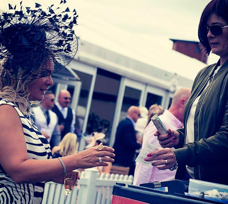 Dressed up lady taking a bet with the bookmakers at Newcastle Racecourse.