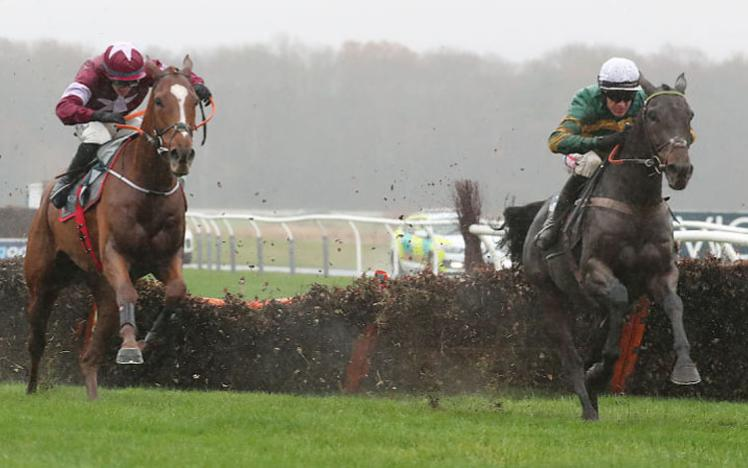 Two horses and jockeys jumping a fence