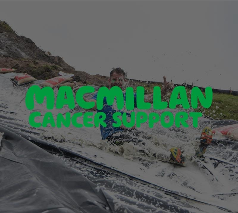 A man in fitness gear slides down a Stampede obstacle.  A logo for Macmillan Cancer Support shows in the foreground.