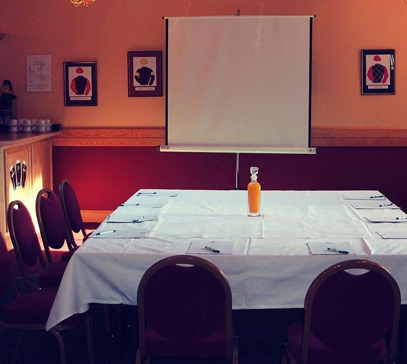 A smaller meeting room with whiteboard.  A bottle of Orange Juice rests on the table.